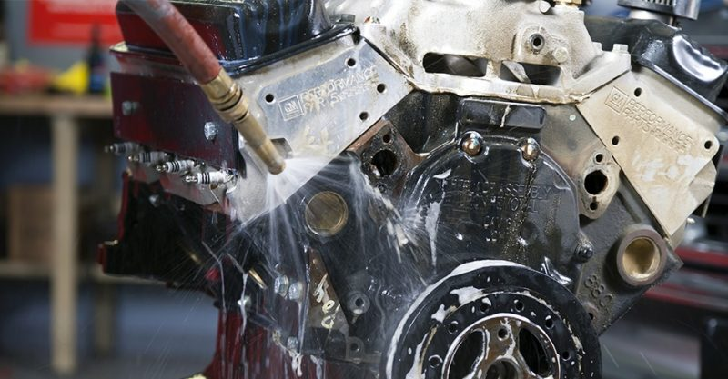 Washing an engine. Vesco offers parts washing services in Michigan.